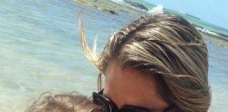 Mãe abraçando e beijando o rosto de uma criança. Eles estão numa praia e o rosto da criança está desfocado.