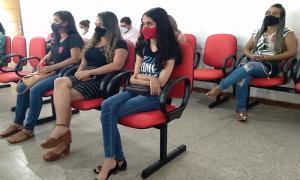 Foto do auditório do centro Cultural onde aparece sentadas lado a lado em cadeiras vermelhas, a Grasiella, Joana Darc e Gabriella, sentada atrás está a Silvana.